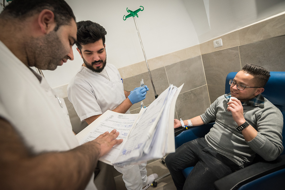 24 February 2020, Jerusalem: Nurses go through their protocols under the lead of Jawad Abu Sahba (centre) from Hebron, before 21-year-old Fadi Taqatqa from Bethlehem receives Chemotherapy treatment at the Augusta Victoria Hospital.