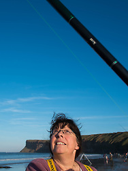 © Licensed to London News Pictures. <br /> 12/10/2014. <br /> <br /> Saltburn, United Kingdom<br /> <br /> Vanessa Barking from Redcar keeps an eye on her fishing line during the annual Jim Maidens memorial beach fishing competition in Saltburn by the Sea in Cleveland. <br /> The competition is held each year to mark the death of Saltburn plumber and keen fisherman Jim Maidens who died in 1998 when he was killed after being swept overboard from his boat 'Corina' close to the beach at Saltburn.<br /> <br /> Photo credit : Ian Forsyth/LNP