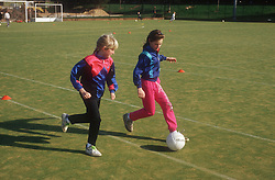Two young girls playing game of football on artificial pitch,