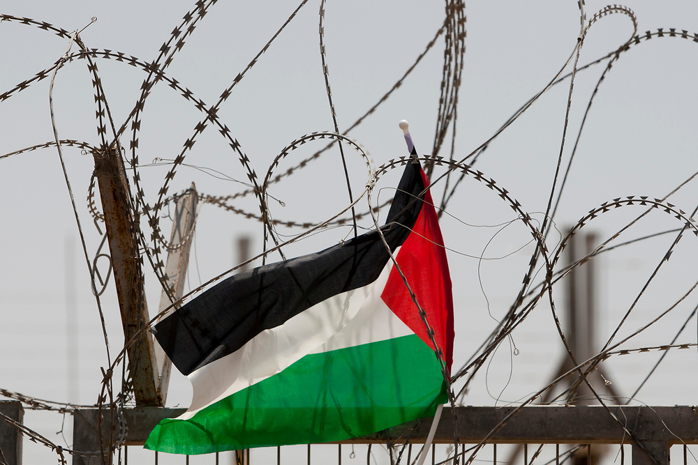 Palestine's flag hangs from an Israeli controlled fence, during a protest against Israel's separation barrier in the West Bank village of Beit Nuba on June 04, 2010.