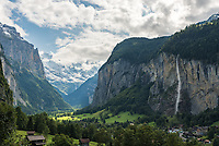 """It's difficult to find a village with a more beautiful view than that of Lauterbrunnen, Switzerland. Set in a deep valley in the Bernese Alps, the name of the town means """"many fountains."""" There are said to be 72 waterfalls cascading over the sheer cliffs into the valley, and it seems the sound of falling water is never out of earshot. The largest waterfall is Staubbach Falls (on the right) and at 300 meters, it's one of the highest unbroken waterfalls in Europe. At the head of the valley is Grosshorn which was covered by a fresh snowfall the day before."""