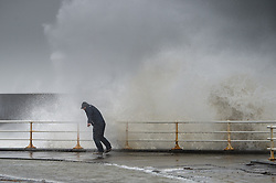 """© London News Pictures. 08/02/2014. Aberystwyth, UK. <br /> 43 year old RUSSEL THOMAS, from Worcester, attempts do dodge a huge wave as gale force winds strike the sea walls at Aberystwyth, Wales at high tide. The winds are forecast to strengthen throughout the day, gusting up to 70 or 80 mph, and with the rising tide, their impact could be potentially damaging again. An amber """"be prepared"""" warning  has been issued by the Met Office for wind,. Photo credit: Keith Morris/LNP"""