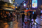 On a rainy night in Soho, Londoners walk across a pedestrianised Old Compton Street at a time when recently re-opened bars and restaurants are desperate for customer business during the coronavirus pandemic, on 27th August 2020, in London, England.