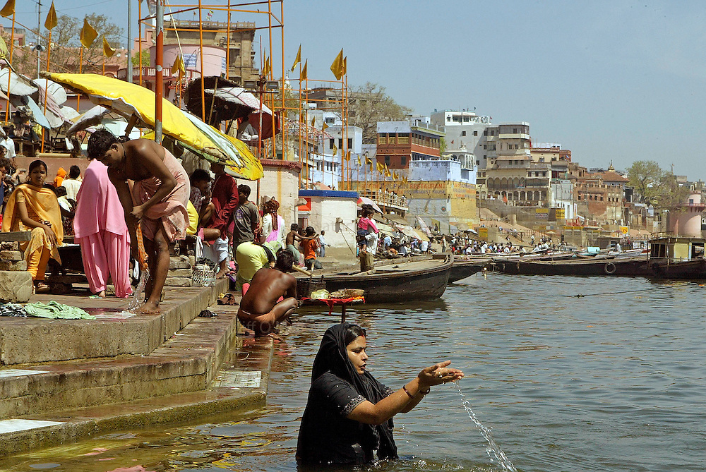 """Varanasi, India. Friday 16 March.A Pilgrim bathes in Varanasi, one of the holiest cities in India is situated on the western bank of the Ganges River and attracts Hindu pilgrims from across the Globe who come to the Varanasi ghats (steps) to bathe in the waters of Ma Ganga..  Alongside the bathing ghats are also """"burning ghats"""" where bodies are cremated in public, the ashes then given to the waters..     The Ganges river is 1557 miles long and stretches from the Himalayas to the Indian Port of Calcutta, supplying water to one twelth of the worlds population. ."""