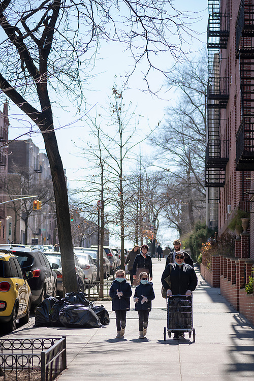 New York City, USA - March 19, 2020: Two children and a woman wearing face masks and latex gloves walk in the Washington Heights neighborhood of Upper Manhattan. Days earlier the city declared a state of emergency due to the growing coronavirus pandemic.