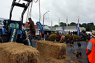 Hunterville, New Zealand - October 27, 2018 - Shepherds have to swing between two bales of hay during the annual Shemozzle obstacle race -- and event that sees the canines and shepherds tackkle mudslides, ride in wheel barrows and carry bulls testicles. The annual Shemozzle race draws thousands every year to this town of less than 500 people. Picture: Giordano Stolley