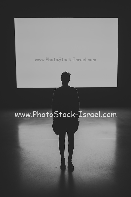 dramatic black and white image of a Silhouette of a female human figure standing with back to camera with an illuminated screen in the background