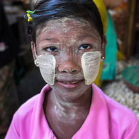 BAGAN, MYANMAR - CIRCA DECEMBER 2013: Portrait of child wearing typical burmese thanaka makeup in the  Nyaung U market close to Bagan in Myanmar