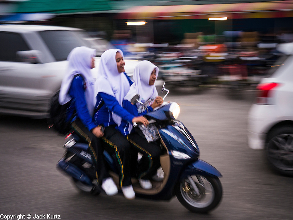 08 JULY 2013 - PATTANI, PATTANI, THAILAND:  Thai Muslim school girls on a motorcycle drive past crowded seafood barbecue restaurants in Pattani, Thailand, Monday, the day before Ramadan. Ramadan starts July 9 and Monday was the last day observant Muslims were able to eat and drink during daylight hours. Muslims fast during the holy month of Ramadan, taking breakfast before dawn and not eating again until after sunset. The restaurants in Pattani, a Muslim majority city in southern Thailand, were packed Monday afternoon and evening.  PHOTO BY JACK KURTZ