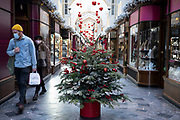 Christmastrees and decorations in Burlington Arcade as people wearing face masks while out shopping and Londoners await the imminent end of the second coronavirus national lockdown before the capital enters tier two in the new three tier system on 1st December 2020 in London, United Kingdom. Non essential shops will be allowed to reopen as of 2nd December while in other areas of the country, controversially, they will have to remain closed. photo by Mike Kemp/In Pictures via Getty Images