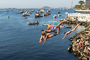 Boys jump into the water from a bridge along the Avenue Portugal into Guanabara Bay in the Urca neighborhood August 26, 2016 in Rio de Janeiro, Brazil. The city is returning to normal following the Olympic games which ended last Sunday.