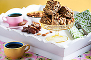 Rodney Bedsole Photography food photographer almond date nut blondies on a white tray with pink and yellow coffee cups.
