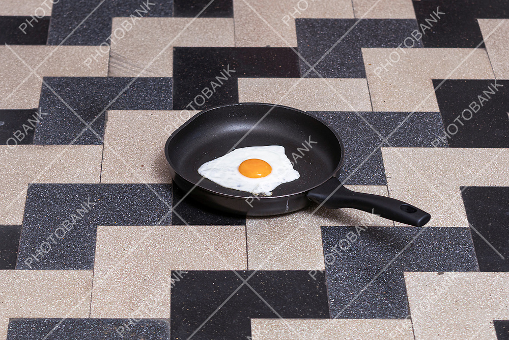 egg cooked in a black pot on a black and gray tile floor