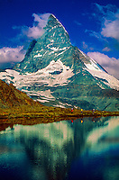 Hikers pass behind the Riffelsee with the Matterhorn behind, Zermatt, Switzerland.