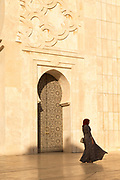 Side view of woman wearing traditional clothing standing in front of Hassan II Mosque, Casablanca, Morocco