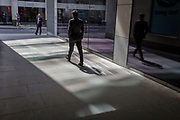 City workers walk through a covered walkway where reflected light from office plate glass leaves shadows, on 19th April, in the City of London, England.
