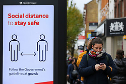 © Licensed to London News Pictures. 30/10/2020. London, UK. A woman wearing a face covering walks past a 'Social Distance to stay safe' sign in north London. Pressure is mounting on the Prime Minister Boris Johnson and Ministers to impose a second national lockdown and London is likely to go into Tier 3 in the coming weeks as coronavirus cases are increasing. Photo credit: Dinendra Haria/LNP