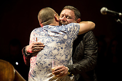 """© Licensed to London News Pictures . 05/02/2016 . Manchester , UK . NICKY LOCKETT ( MC Tunes ) and SHAUN RYDER hug on stage . """" Hacienda Classical """" debut at the Bridgewater Hall . The 70 piece Manchester Camerata and performers including New Order's Peter Hook , Shaun Ryder , Rowetta Idah , Bez and Hacienda DJs Graeme Park and Mike Pickering mixing live compositions . Photo credit : Joel Goodman/LNP"""