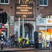 NLD/Amsterdam/20150326 - Cocaine waarshuwingsborden voor toeristen met een alert voor de verkoop van witte heroïne die in omloop is, teksten over de dodelijke slachtoffers die gevallen zijn. Op de borden zijn de volgende teksten te lezen: 'Witte heroïne wordt verkocht aan toeristen als cocaïne', 'Toeristen in het ziekenhuis, waarvan er drie gestorven zijn' en 'Negeer straatdealers, pas op'.                                                       -                                                                    In the center of Amsterdam are bright signs tourists warn of drug dealers. Three tourists were killed when they were white snorted heroin which was sold as cocaine. The full text of the warning reads: Caution! White heroin sold to tourists as cocain. Tourists in hospital three have died. Ignore street dealers. www.drugsalert.nl.
