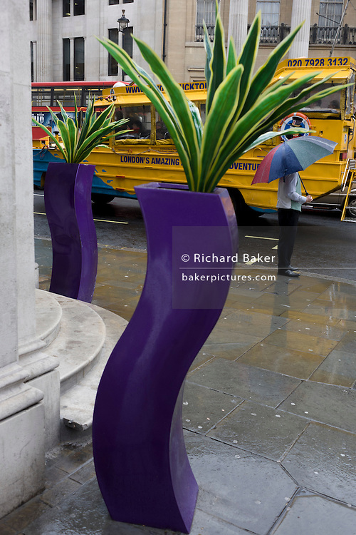 Man stands sheltering from April rain under umbrella near and a pseudo-artistic plant stand feature in central London.