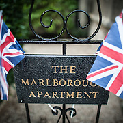 Small Union Flag pennants frame the sign for the historic Marlborough apartment in Royal Crescent in Bath, Somerset, United Kingdom. The Marlborough apartments are a tourist attraction that preserves the interior design of the Edwardian apartments in their heyday.