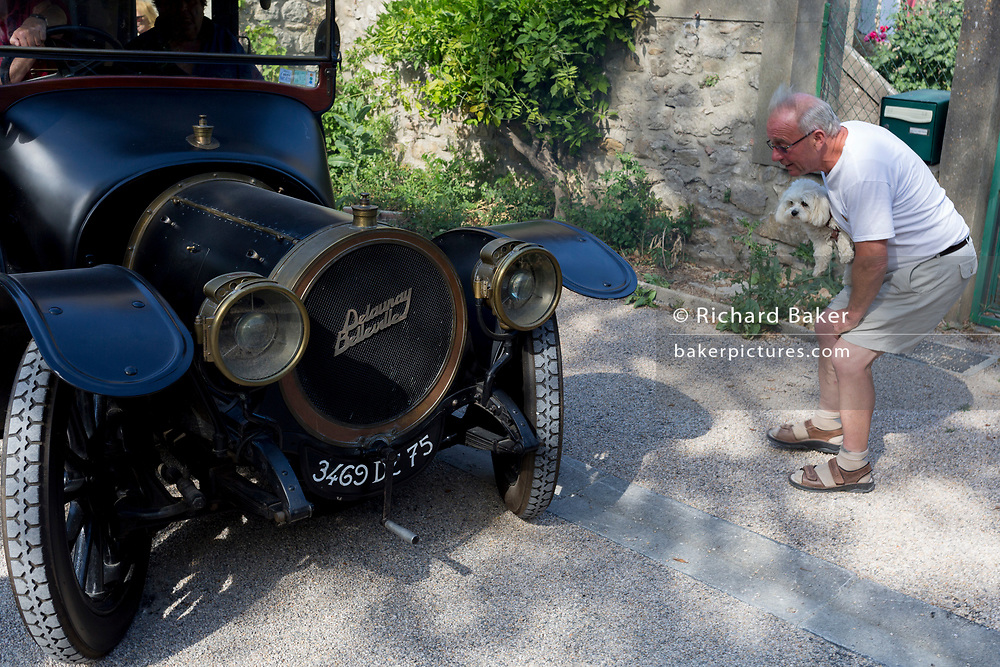 A local frenchman and his pet dog admires a visiting 1912 Delauney Belleville vintage car in a French village, during a three-day rally journey through the Corbieres wine region, on 26th May, 2017, in Lagrasse, Languedoc-Rousillon, south of France. Lagrasse is listed as one of France's most beautiful villages and lies on the famous Route 20 wine route in the Basses-Corbieres region dating to the 13th century.