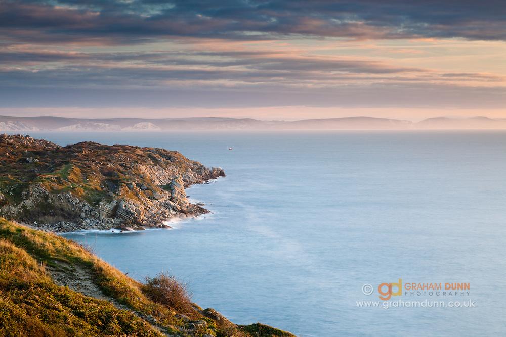 Dawn skies over a misty Dorset coastline, from Portland, England, UK.