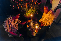 Men playing checkers by candlelight during the monthly Hoi An Full Moon Lantern Festival, Hoi An, Vietnam.
