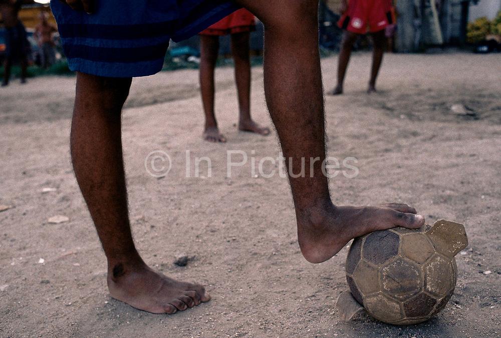 Young boys play football on the streets of favela Jacarezinho, Rio de Janeiro, Brazil