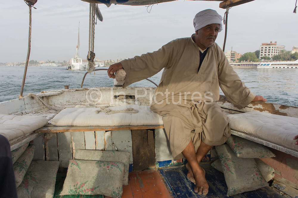 A crewman of a felucca steers his sailing boat while sailing on the River Nile at Luxor, Nile Valley, Egypt. Feluccas are ancient Egyptian sail boats which were used in ancient times as a primary mode of transport and are the only type of boat that is still used extensively in the country. Plying this great African river is a cheap fare state-run ferry used by commuters and locals but these sailing boats serve tourists and therefore are the many victims of the tourism downturn. According to the country's Ministry of Tourism, European visitors to Egypt is down by up to 80% in 2016 from the suspension of flights after the downing of the Russian airliner in Oct 2015. Euro-tourism accounts for 27% of the total flow and in total, tourism accounts for 11.3% of Egypt's GDP.