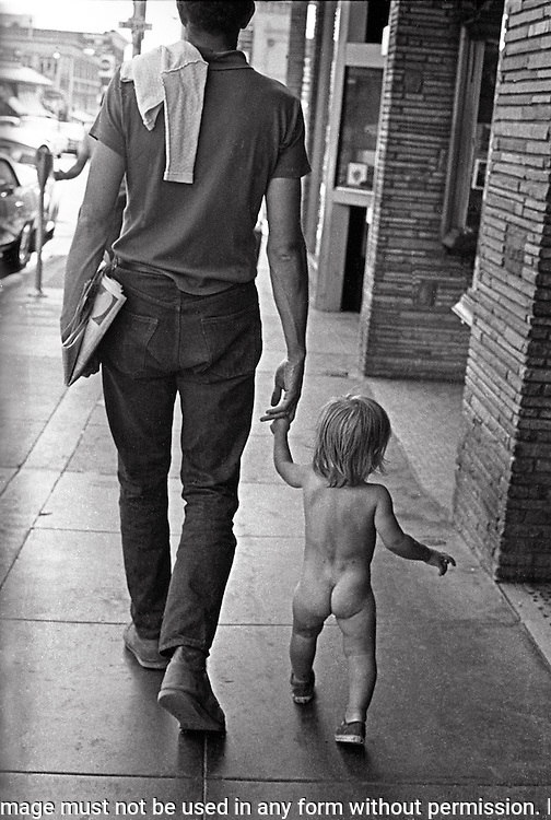 Father and naked toddler walking down street