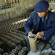 A Bai ethnic minority man makes clay roof tiles by hand, Dian Nan village, Yunnan Province, China
