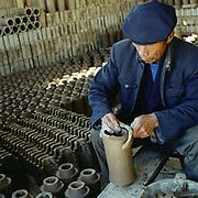 A Bai ethnic minority man makes clay roof tiles by hand, Dian Nan village, Yunnan Province, China