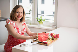 Pregnant woman cutting slices of watermelon in the kitchen, Munich, Bavaria, Germany