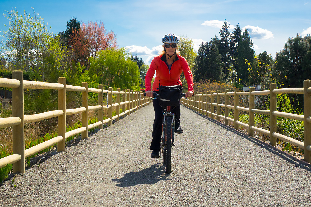 North America, United States, Washington, Kirkland. A woman rides a mountain bike along the Cross Kirkland Corridor, a former railroad line converted to a trail for walking and bicycling.