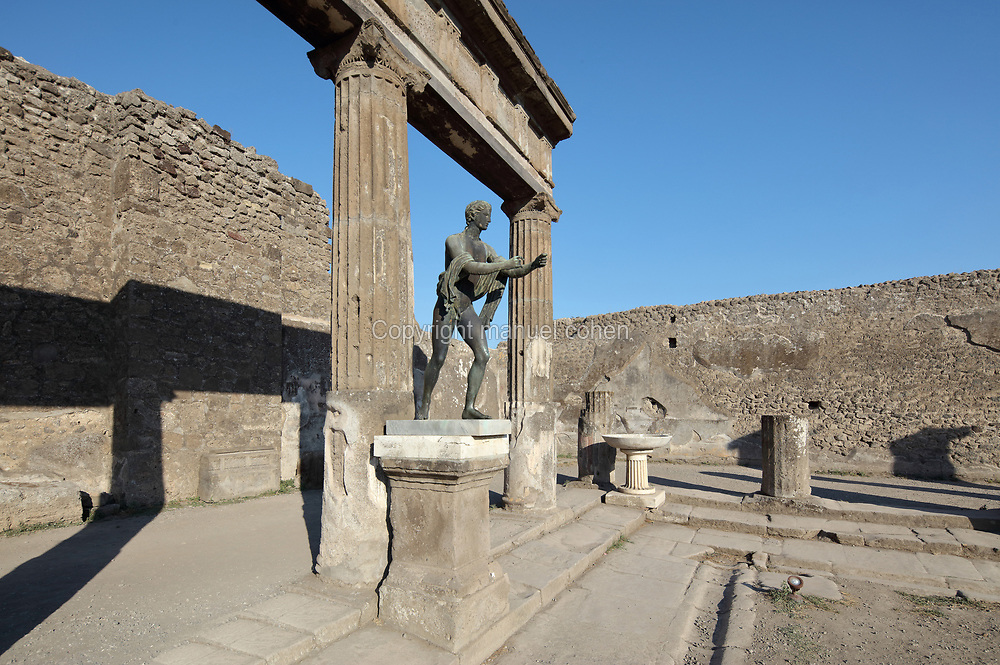 Temple of Apollo, with copy of the original statue of Apollo shooting arrows (the original is in the National Archaeological Museum in Naples), in the Parco Archeologico di Pompei, or Archaeological Park of Pompeii, Campania, Italy. The temple was originally built in the 2nd century BC and was damaged in the 62 AD earthquake. A new phase of official excavations has been taking place here since 2017 in an attempt to stop looters from digging tunnels and removing artefacts for sale. Pompeii was a Roman city which was buried in ash after the eruption of Vesuvius in 79 AD. The site is listed as a UNESCO World Heritage Site. Picture by Manuel Cohen