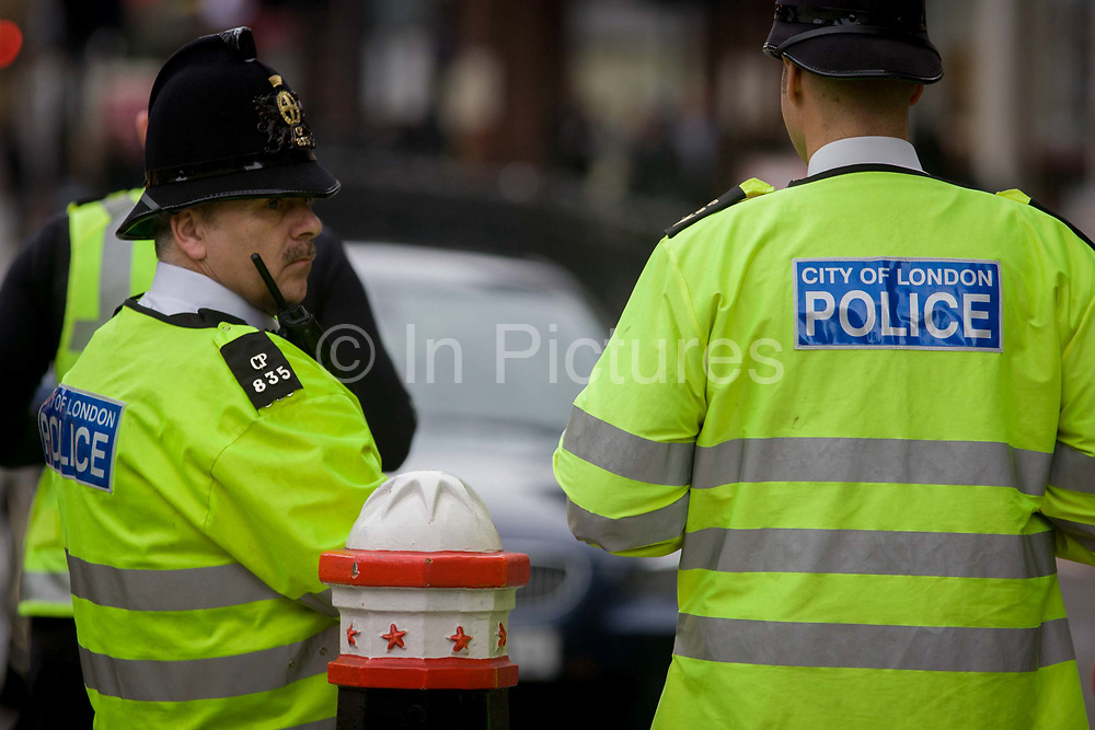 The backs of officers from the City of London police, man a checkpoint looking for suspect vehicles and drivers entering at Aldgate, one the city entrance points into the Square Mile, the capital's financial and historic heart, founded by the Romans in 43AD.
