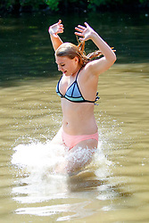 © Licensed to London News Pictures. 05/07/2017. London, UK. Sahra Ash jumps into Hampstead Heath Mixed Bathing Pond in north London as temperatures hit 28C degrees on 5 July 2017. Photo credit: Tolga Akmen/LNP
