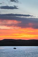 Fishing from boat on  Soda Lake at sunset, Wyoming