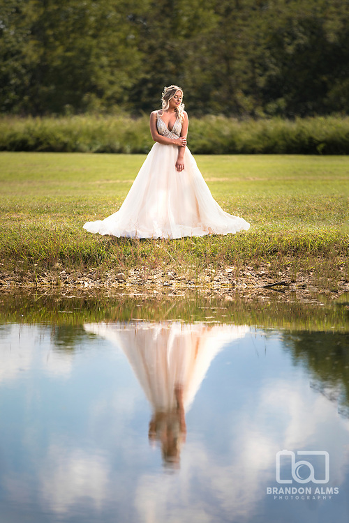 Bride in dress reflecting in a pond photo by Brandon Alms Photography