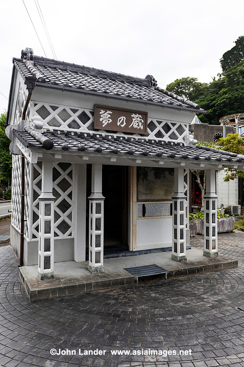 """NamakowallorNamako-kabe is a special Japanese design widely used for vernacular buildings, particularly on fireproof storehouses in the latter half of the Edo Period. Typically, thenamakowall is distinguished by a white grid pattern on charcoal gray slate. Namako kabe literally means """"sea cucumber wall"""" and is a representative type of fireproof wall for traditional Japanese buildings. Namako wall timbers are wrapped with thick earthen layers and the surface is covered with charcoal gray square tiles whose joints are protected by thick white plaster. Therefore namako wall is strong against fire and well in insulation. The black and white diagonal design creates a special symmetry with the rest of the building.  The naming of """"namako"""" wall comes from the recognition that the shape of the joint plaster resembles a sea cucumber. As namako wall was expensive, only rich people could afford it and even those rich people gave priority to cover their kura storehouses with namako. In the center of the main settlement of Matsuzaki, Izu there are dozens of namako wall buildings."""