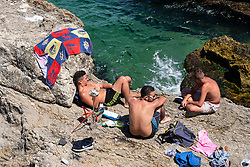Men sunbathing on rocks at Ras Beirut beside The Corniche in Beirut, Lebanon.
