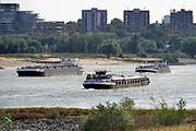 Nederland, Nijmegen, 19-8-2018 Door de aanhoudende droogte staat het water in de rijn, ijssel en waal extreem laag . Schepen moeten minder lading innemen om niet te diep te komen . Hierdoor is het drukker in de smallere vaargeul. Door uitblijven van regenval in het stroomgebied van de rijn komt het record, laagterecord in zicht . Veel mensen vermaken zich op het strand wat door het lage water ontstaan is. Foto: Flip Franssen