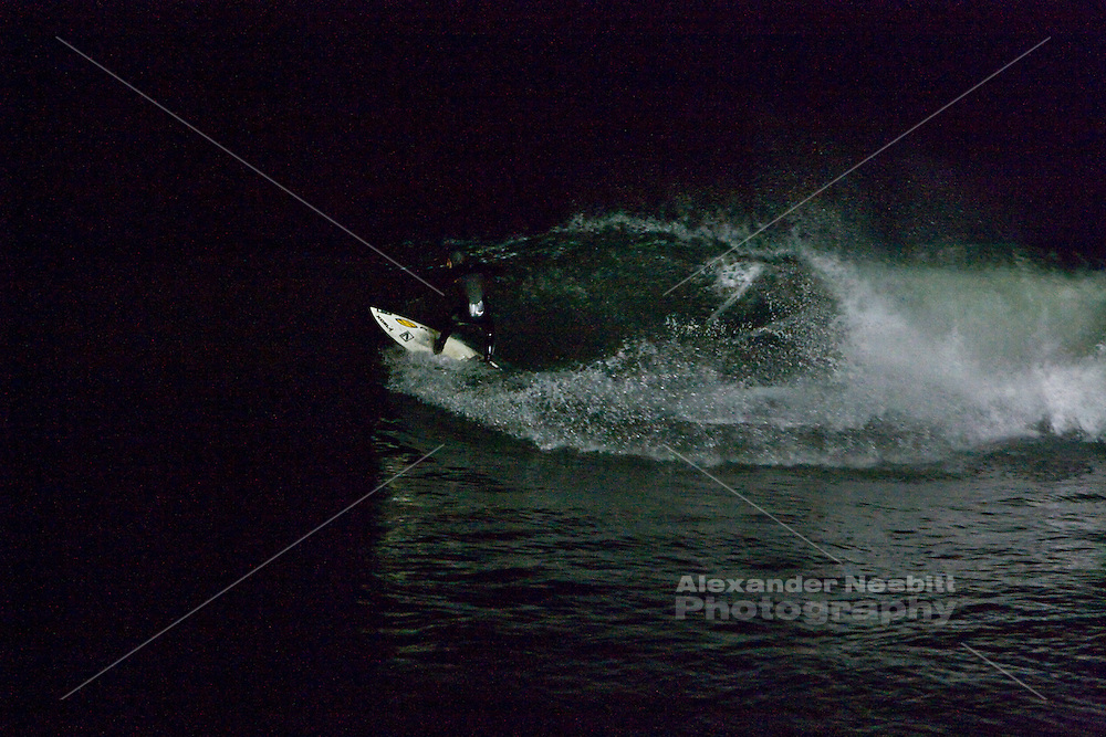 Narragansett, RI - Surfers ride a late night winter storm swell off Monahan's dock using 4 sets of generator powered, road crew lights to illuminate the waves.