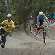 Andre Loo, 20, (centre) from Queenstown, and Ben Tyas (left) from Auckland in action during the Gorge Road Mega Jam, for BMX and Mountain Bike riders to mark the opening  of the Gorge Road Jump Park run by the Queenstown Mountain Bike Club,  Queenstown, New Zealand. 3rd December 2011. Photo Tim Clayton