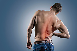 Rear view of shirtless muscular man holding hand to spot of back pain