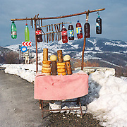 A roadside stall selling locally made cheese, sausage and fruit juices on the Rucar pass in the Carpathian Mountains, Romania. Some of the actual produce on this roadside stall is replaced by wooden replicas so they won't spoil in the sun.