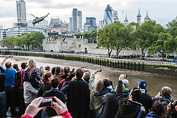 © Licensed to London News Pictures. 20/07/2012. London, UK.  London 2012 Olympics.  Crowds of spectators line Tower bridge as the Olympic Torch arrives in London, flown by Royal Navy Sea King helicopter to the Tower of London and abseiled down by a Royal Marine Commando.   Here the helicopter flies off after delivering its load.  Photo credit : Richard Isaac/LNP