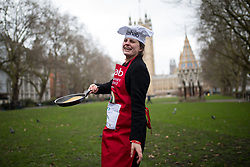 © Licensed to London News Pictures. 13/02/2018. London, UK. Laura Hughes of the Media team practises ahead of the Rehab Parliamentary Pancake Race 2018 in Victoria Tower Gardens. The Parliament Team - made up of MPs, Lords and Ladies - race in a relay against the Media Team - made up of reporters and presenters - whilst continuously flipping pancakes to celebrate Shrove Tuesday, also known as Pancake Day. Photo credit : Tom Nicholson/LNP