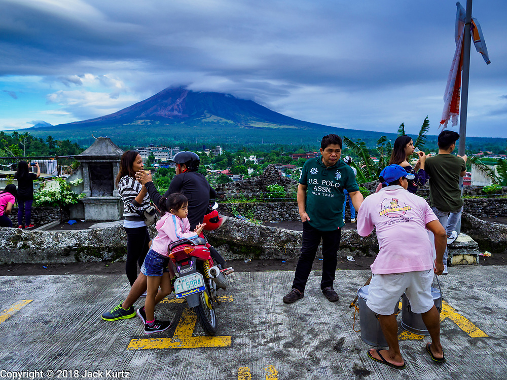 21 JANUARY 2018 - LEGAZPI, ALBAY, PHILIPPINES: People relax on the volcano overlook at Our Lady of the Gate Parish (Parroquia Nuestra Señora de la Porteria), while the Mayon volcano releases smokes and ash Sunday morning. Mayon is the most active volcano in the Philippines. More than 30,000 people have been evacuated from communities on the near the Mayon volcano in Albay province in the Philippines. Most of the evacuees are staying at schools in communities outside of the evacuation zone.    PHOTO BY JACK KURTZ